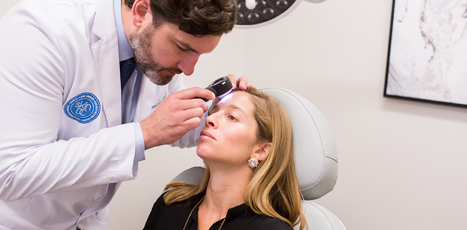 doctor looking/screening for skin cancer