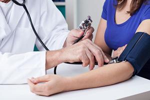 Provider checks blood pressure of patient.