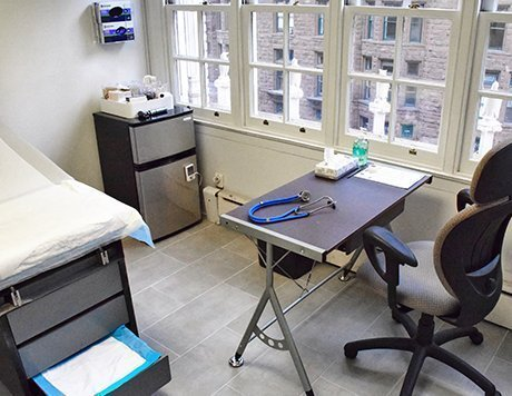 Exam room featuring exam table, window and a desk with a stethoscope on it.