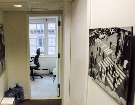 View of exam room from the hallway, with just a glimpse of an office chair and a black and white photo of New York City in the foreground.