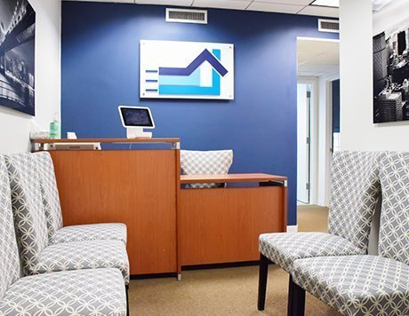 Waiting room featuring a prominent blue wall with a Bethany Medical Clinic logo and rows of chairs.