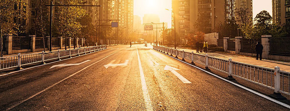 Hazy yellow sun stretches out across a New York City street and pours over residential high rises and pedestrians. Everything points forward towards the sun.