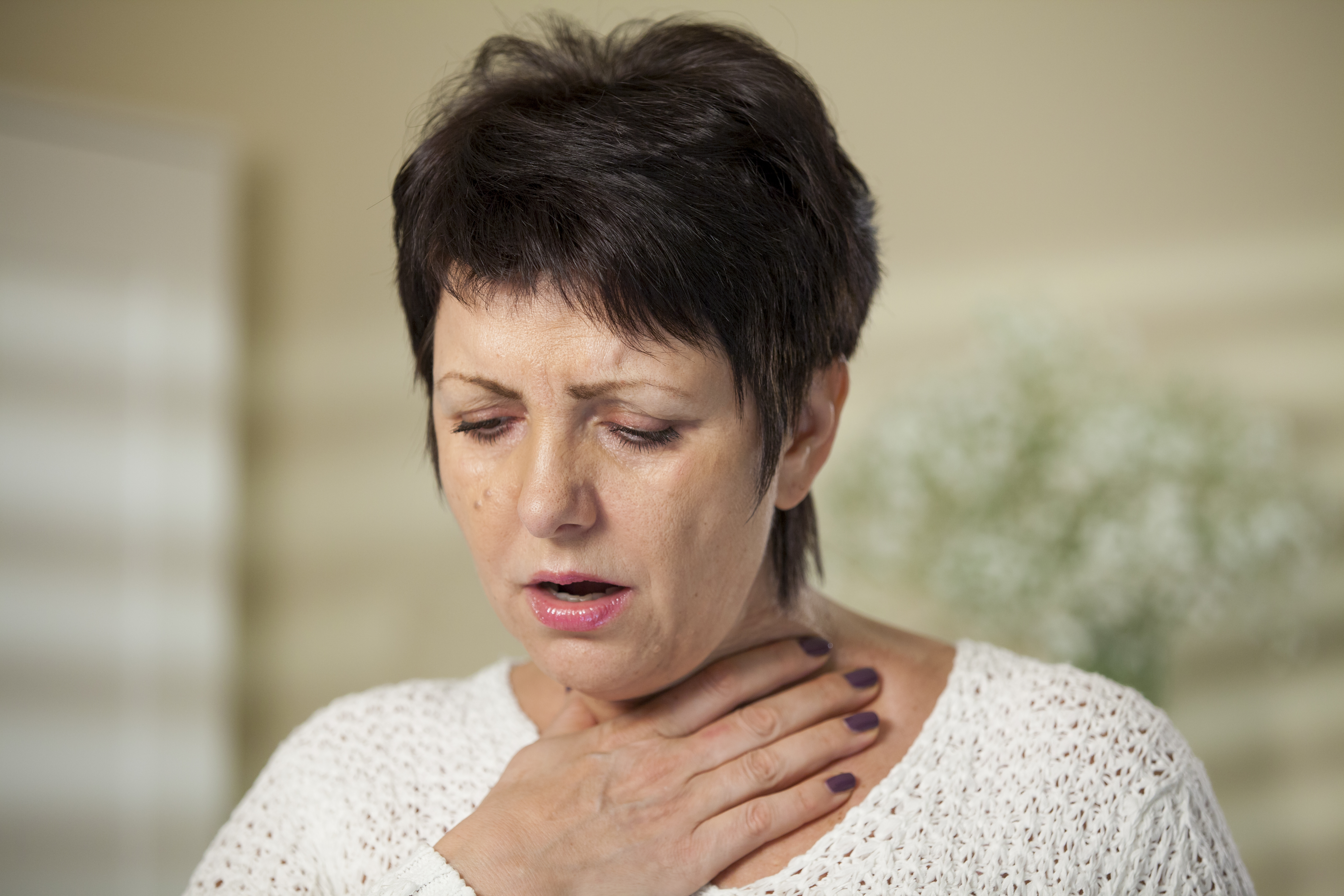 woman holding throat from asthma attack